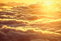 Bright sun shining from behind a bed of puffy yellow clouds at sunset sky