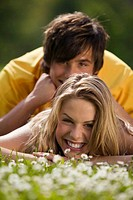 Young couple lying in meadow, smiling, close-up, portrait