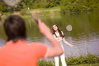 Young couple playing badminton, focus on woman