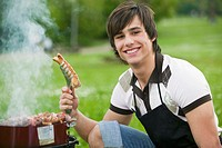 Young man holding grilled sausage, smiling, close-up