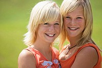Two teenage girls (13-15) smiling, portrait, close-up