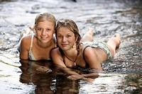 Two teenage girls (13-14) lying in river, close-up, portrait