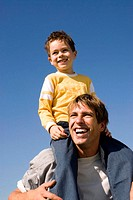 Boy (4-7) sitting on father's shoulders, smiling, close-up
