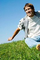 Mid adult man sitting in park biting grass, smiling, low angle view