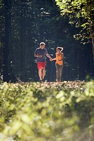 Young couple jogging in forest, holding hands