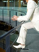 Businesswoman leaning on handrail