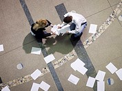 Couple in hall collecting papers, elevated view