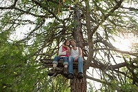 Young couple sitting on tree house, embracing, low angle view