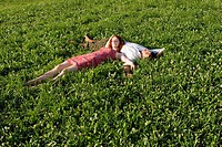 Woman lying with head on man`s belly in meadow