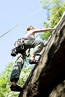 Young woman mountain climbing, low angle view