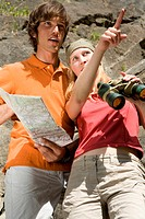 Young couple with map and binoculars, woman pointing, low angle view