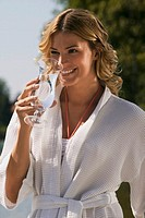 Woman wearing bath robe, holding glass of water