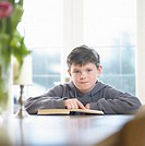 Boy (9-11) sitting with book at table