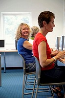 Three mature women in computer room, one turning round, portrait
