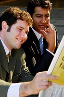 2 young male business men sitting together reading paper
