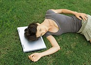 Woman lying in grass, head resting on laptop computer