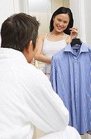 Woman standing in front of seated man, holding shirt on a hanger