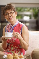 Mature woman at home, holding cup and saucer
