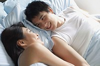 Couple in bed, looking at each other, smiling