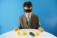 Blindfolded businessman sitting in front of three lemons and a model toy car