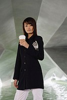 Woman in black jacket, holding disposable coffee cup and newspaper
