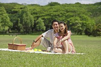 Couple sitting in park, having a picnic, looking at camera