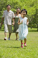 Family with one child walking in park, daughter running in foreground