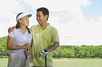 Couple standing side by side, holding golf clubs, looking at each other