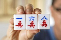 Close-up of mahjong tiles with Chinese characters for One, Six and Eight