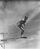 Man standing on springboard, preparing to dive, (B&W)