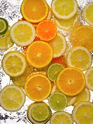 Slices of lemon, limes and oranges in water, close-up, cross section