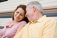 Mature couple sitting near a caravan (thumbnail)