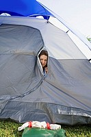 Mature woman peering from tent