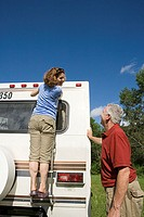 Mature couple preparing caravan for journey