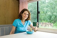 Woman having breakfast in a caravan
