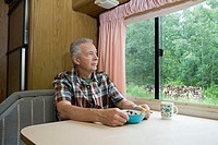 Man having breakfast in a caravan