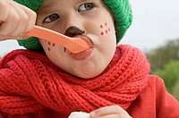 Boy in scarf and hat eating