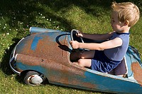 Boy in an old toy car