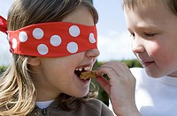 Boy feeding biscuit to girl in a blindfold