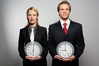 Businesspeople holding clocks