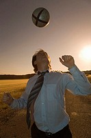 Businessman playing with ball in field