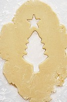 Rolled cookie dough with a Christmas tree and star cut out