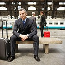 Businessman Sitting on Bench on Train Platform