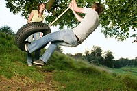 Teenage Couple Playing on Rope Swing