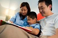 Asian Couple Reading to Son
