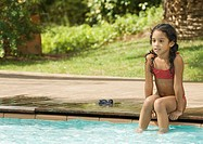 Girl sitting on edge of swimming pool with feet in water