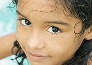 Little girl with wet face, pool water in background, close-up