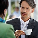 Man Holding Coffee and Talking to Woman