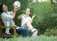 Girl and grandfather sitting together, playing with soccer ball