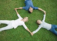 Mature couple and granddaughter lying on grass, holding hands